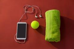 Vue aérienne de balle de tennis parmi la serviette et de téléphone portable avec des écouteurs de dans-oreille Photos libres de droits