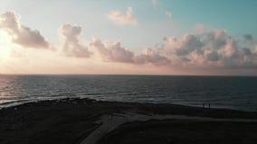 Vue aérienne de beau chemin piétonnier avec des touristes marchant par la plage rocheuse au coucher du soleil avec l'océan à l'ho banque de vidéos