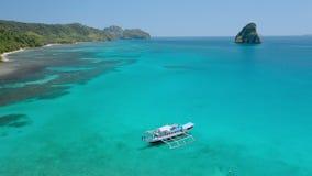 Vue aérienne de bourdon entourant autour du bateau de voyage d'île en île amarré en eau peu profonde dans la lagune de Cadlao de  banque de vidéos