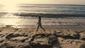 Vue aérienne de bourdon de jeune femme en bonne santé dans la robe fonctionnant sur la plage tropicale près de l'océan pendant le photos stock