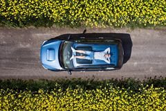 Vue aérienne de bourdon de l'homme détendant sur le toit de voiture image libre de droits