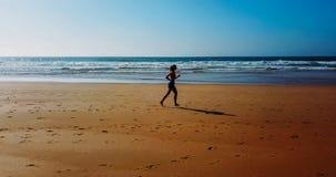 Vue aérienne de bourdon de la femme folâtre en bonne santé courant sur la plage Photographie stock