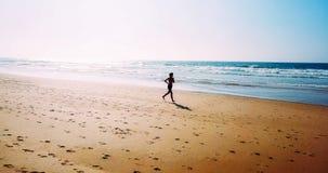 Vue aérienne de bourdon de la femme folâtre en bonne santé courant sur la plage Photo libre de droits