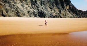 Vue aérienne de bourdon de la femme folâtre en bonne santé courant sur la plage Images libres de droits