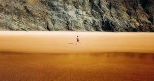 Vue aérienne de bourdon de la femme folâtre en bonne santé courant sur la plage Photo stock