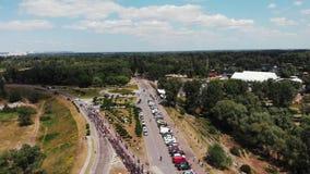 Vue aérienne de bourdon de parc récréationnel vert avec le groupe de jeunes cavaliers de vélo et parkings Le groupe de cyclistes  clips vidéos