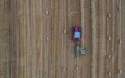 Vue aérienne de bourdon de tracteur fonctionnant dans un domaine de blé créant des balles de paille, meules de foin image stock