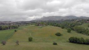 Vue aérienne de bourdon vers le haut de campagne au-dessus des collines et des forêts et des horizons de village banque de vidéos