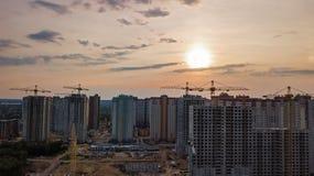 Vue aérienne de chantier de construction des bâtiments de zone résidentielle avec des grues au coucher du soleil d'en haut, horiz Photos stock