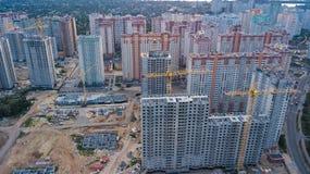 Vue aérienne de chantier de construction des bâtiments de zone résidentielle avec des grues au coucher du soleil d'en haut, horiz Photographie stock