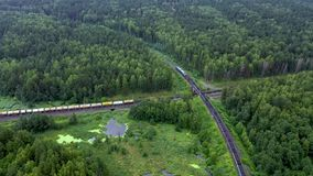Vue aérienne de deux trains de fret croiser perpendiculairement au milieu de la forêt, à côté d'un lac marécageux E banque de vidéos