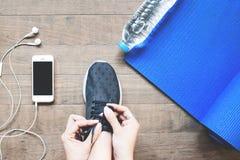 Vue aérienne de femme dans l'espadrille noire avec le smartphone et l'équipement de sport sur le bois Photo stock