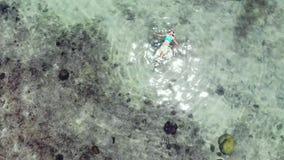 Vue aérienne de femme flottant en stupéfiant les eaux claires sur l'île tropicale Beau soleil reflété en mer banque de vidéos