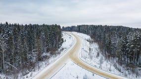 Vue aérienne de forêt couverte de neige, route dans l'horaire d'hiver photo libre de droits