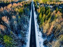 Vue aérienne de forêt neigeuse avec une route Capturé de ci-dessus avec un bourdon images stock