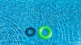 Vue aérienne de jouet gonflable coloré de beignet d'anneau dans l'eau de piscine d'en haut photographie stock libre de droits