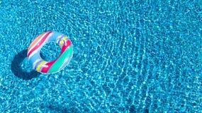 Vue aérienne de jouet gonflable coloré de beignet d'anneau dans l'eau de piscine d'en haut, concept de vacances de famille images libres de droits