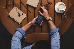 vue aérienne de l'homme à l'aide du smartphone avec le site Web de facebook tout en se reposant à la table avec du café photographie stock libre de droits