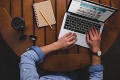 vue aérienne de l'homme à l'aide de l'ordinateur portable avec l'amazonwebsite tout en se reposant à la table avec du café photo stock