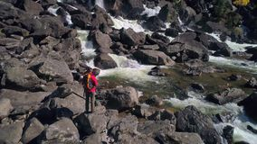 Vue aérienne de l'homme se tenant devant une rivière de cascade avec des roches, rivière banque de vidéos