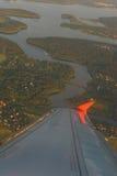 Vue aérienne de la fenêtre d'une avion de ligne de passager en vol aux nuages dans les rayons le Soleil Levant Image stock