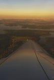 Vue aérienne de la fenêtre d'une avion de ligne de passager en vol aux nuages dans les rayons le Soleil Levant Photographie stock libre de droits
