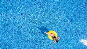 Vue aérienne de la jeune natation de femme de brune sur le grand anneau jaune gonflable dans la piscine image libre de droits