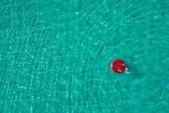Vue aérienne de la natation mince de femme sur le beignet d'anneau de bain en mer transparente de turquoise en Seychelles Paysage photographie stock