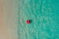 Vue aérienne de la natation mince de femme sur le beignet d'anneau de bain en mer transparente de turquoise en Seychelles Paysage photo libre de droits