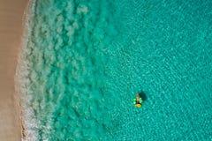Vue aérienne de la natation mince de femme sur le beignet d'anneau de bain en mer transparente de turquoise en Seychelles Paysage image libre de droits