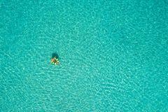 Vue aérienne de la natation mince de femme sur le beignet d'anneau de bain en mer transparente de turquoise en Seychelles Paysage images libres de droits