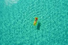 Vue aérienne de la natation mince de femme sur le matelas de bain en mer transparente de turquoise en Seychelles Paysage marin d' photos stock