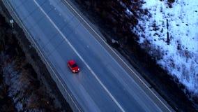 Vue aérienne de la voiture rouge qui monte sur un échange énorme au coucher du soleil banque de vidéos