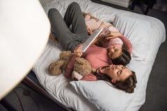 vue aérienne de mère et de fille à l'aide du comprimé ensemble tout en se trouvant sur le lit image stock