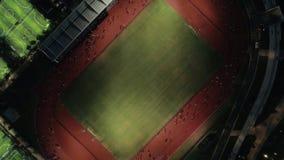 Vue aérienne de nuit de bourdon de voie courante avec les personnes courantes Voie courante de stade à où l'athlétisme s'exercent banque de vidéos