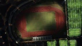 Vue aérienne de nuit de bourdon de voie courante avec les personnes courantes Voie courante de stade à où l'athlétisme s'exercent clips vidéos