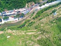 Vue aérienne de pente de montagne avec peu de village et rivière pendant la saison d'été photographie stock