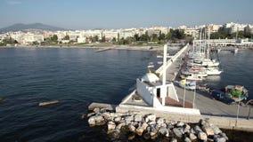 Vue aérienne de petite église orthodoxe grecque blanche au bord de la marina pour des bateaux dans Kalamaria Salonique Grèce, MOI clips vidéos