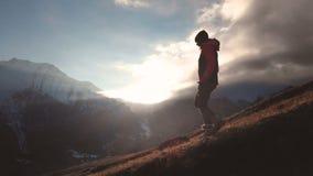 Vue aérienne de possibilité éloignée d'un tir épique d'une fille marchant au bord d'une montagne comme silhouette dans un beau co banque de vidéos