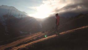 Vue aérienne de possibilité éloignée même d'un tir épique d'une fille marchant au bord d'une montagne comme silhouette dans un be banque de vidéos