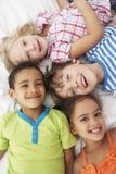 Vue aérienne de quatre enfants jouant sur le lit ensemble Photographie stock libre de droits