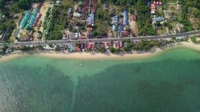 Vue aérienne de région de Residental avec le logement et de transport se déplaçant le long de la route près de Sandy Beach et du  banque de vidéos