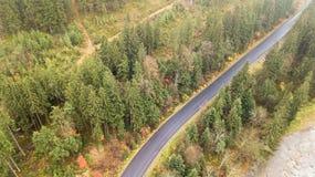 Vue aérienne de route au milieu des montagnes, sur lesquelles les pins se développent Photo stock