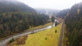 Vue aérienne de route au milieu des montagnes, sur lesquelles les pins se développent Photographie stock libre de droits