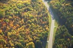 Vue aérienne de route courbant par des bois dans la couleur de chute images libres de droits