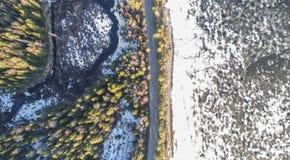 Vue aérienne de route rurale de ressort dans la forêt de pin jaune avec le lac de fonte de glace images libres de droits