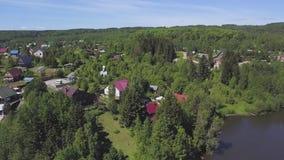 Vue aérienne de secteur suburbain avec beaucoup d'arbres verts et une route sous le ciel d'été clip Petite ville parmi boisé banque de vidéos