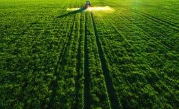 Vue aérienne de tracteur de ferme labourant et pulvérisant sur le champ Images libres de droits