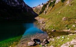 Vue aérienne de type refroidissant dans un hamac entre deux pierres à un lac de montagne enjoing la vue photos stock