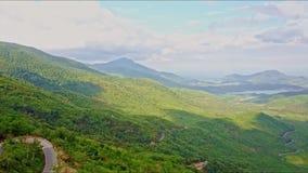 Vue aérienne de vallée des montagnes verte avec la courbe dans la route banque de vidéos